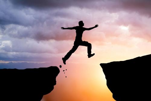 Gray-stone-advisors-man-jumping-over-gap-sunset